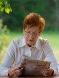 玻璃的妇女观看一本杂志户外 免版税库存图片