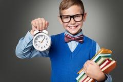 玻璃的小学生与闹钟和书,聪明的孩子 免版税库存照片