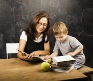 玻璃的小逗人喜爱的男孩与年轻真正的老师,教室学习 库存图片