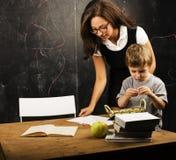 玻璃的小逗人喜爱的男孩与年轻真正的老师,教室学习 免版税库存照片
