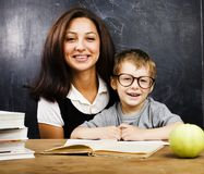 玻璃的小逗人喜爱的男孩与年轻真正的老师,教室学习 图库摄影