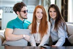 玻璃的年轻人与cusion在看两个漂亮的女人的手上 图库摄影