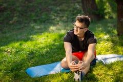 玻璃的年轻人训练瑜伽的户外 运动的人在一张蓝色瑜伽席子做放松的锻炼,在公园 r 库存照片