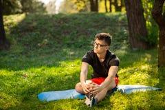 玻璃的年轻人训练瑜伽的户外 运动的人在一张蓝色瑜伽席子做放松的锻炼,在公园 r 图库摄影