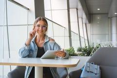 玻璃的年轻女人工作在咖啡馆的一张桌上 免版税库存照片