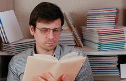 玻璃的年轻深色的人读坐在书中的一本书 免版税库存照片
