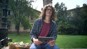 玻璃的年轻英俊的人与看卷曲长的头发拿着片剂和,坐长凳在公园近 股票视频