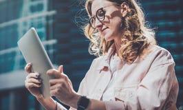 玻璃的年轻行家女实业家在他的屏幕上在她的手上拿着片剂计算机并且读信息 库存图片