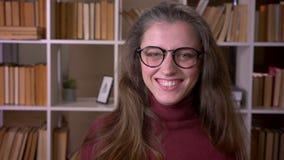 玻璃的微笑与混乱的年轻白种人女生特写镜头画象看照相机在学院 影视素材