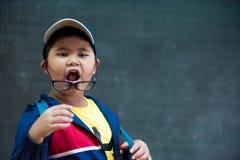 玻璃的愉快的微笑的亚裔男孩上学 免版税库存照片