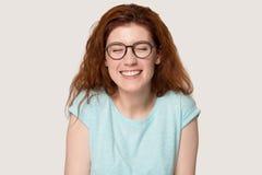 玻璃的愉快的红发女孩嘲笑滑稽的笑话 库存图片