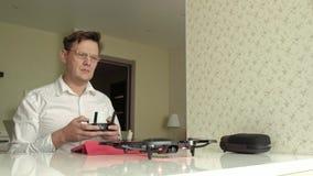 玻璃的成熟人和白色衬衫从控制台的控制quadcopter,试验飞行,学习的概念 股票录像