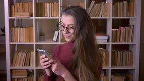 玻璃的浏览在电话的年轻白种人女生特写镜头画象微笑愉快地看照相机  股票视频