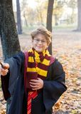 玻璃的男孩在有陆军少校的肩章的秋天公园在黑长袍在他的手上站立,拿着书,佩带 哈利波特样式 免版税图库摄影