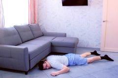 玻璃的疲倦的滑稽的书呆子人和短裤在家falled对从精疲力尽的地板 免版税库存图片