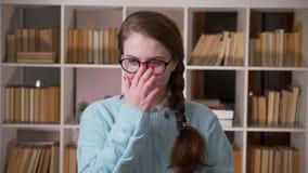玻璃的看照相机微笑在大学图书馆里的年轻俏丽的女生特写镜头画象户内 影视素材