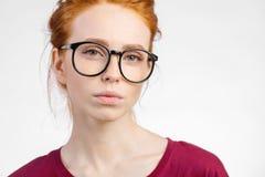 玻璃的红头发人妇女与看在白色背景的头发结照相机 免版税图库摄影