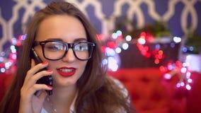 玻璃的美丽的妇女谈话在咖啡馆, 4 k的手机 智能手机妇女谈话在电话,当坐在咖啡馆时 股票视频