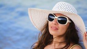 玻璃的美丽的少妇晒日光浴在海滩的反对海 股票视频