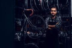 玻璃的英俊的有胡子的人站立靠近固定的自行车在他自己的车间 库存图片