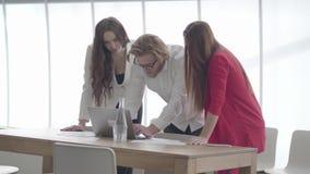 玻璃的英俊的白肤金发的人弯曲在netbook在显示信息的一个轻的舒适的办公室对女性同事 股票视频