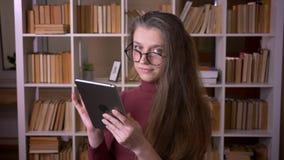 玻璃的输入在片剂的年轻白种人女生特写镜头画象户内大学图书馆 影视素材