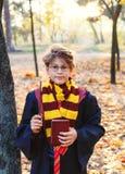 玻璃的逗人喜爱的男孩在有陆军少校的肩章的秋天公园在黑长袍在他的手上站立,拿着书,佩带 免版税库存图片