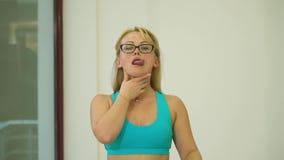 玻璃的金发碧眼的女人显示如何做舌头的准备 影视素材