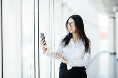 玻璃的键入文本电话的一个年轻女商人的画象反对全景窗口 到达天空的企业概念金黄回归键所有权 免版税库存照片