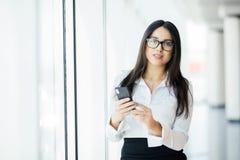 玻璃的键入文本电话的一个年轻女商人的画象反对全景窗口 到达天空的企业概念金黄回归键所有权 免版税库存图片
