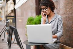 玻璃的非裔美国人的女孩坐长凳和谈话在她的手机,当工作在膝上型计算机时 小姐与 免版税库存照片