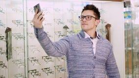 玻璃的,眼镜性感的英俊的年轻人在光学商店做selfie,光学,眼镜师零售店,镜片 股票视频