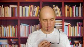 玻璃看书的想法的人在书橱背景的家庭书库里 沉思人读书文件在舒适家 影视素材