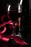 玻璃红色丝带酒 免版税库存图片