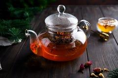 玻璃茶壶用新近地酿造的清凉茶和蜂蜜在木背景 温暖的圣诞节或热的冬天饮料 库存图片