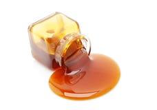 玻璃蜂蜜瓶子溢出 免版税库存图片