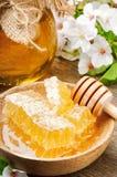 玻璃蜂蜜罐和蜂蜜梳子 库存图片