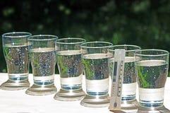 玻璃行与水和显示30多摄氏度的温度计的 库存图片