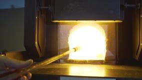 玻璃设计工在他的采取有液体玻璃的车间标尺在发光的热的烤箱外面 股票视频