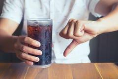 玻璃软性饮料在手边飞溅与冰木桌backg 免版税库存照片
