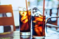 玻璃软性饮料飞溅与新鲜的冰在木桌后面 免版税库存照片