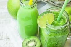 玻璃金属螺盖玻璃瓶和瓶有绿色菜的和果子圆滑的人和汁与秸杆 与季节性有机产物的篮子 库存图片