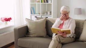 玻璃阅读书的资深妇女在家 影视素材