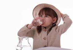 玻璃饮料的女孩一点坐水 免版税库存照片