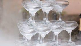 玻璃香槟抽烟 香槟构成的玻璃水平地射击了 滚滚向前在香槟槽的烟 承办酒席服务 婚姻的幻灯片 库存图片