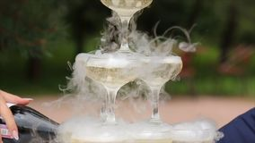 玻璃香槟抽烟 香槟构成的玻璃水平地射击了 滚滚向前在香槟槽的烟 承办酒席服务 婚姻的幻灯片 库存照片