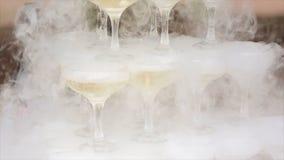 玻璃香槟抽烟 香槟构成的玻璃水平地射击了 滚滚向前在香槟槽的烟 承办酒席服务 婚姻的幻灯片 图库摄影