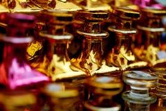 玻璃香水瓶根据油 义卖市场,市场 宏指令 金子和桃红色伽玛 库存照片