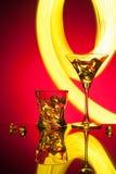 玻璃鸡尾酒马蒂尼鸡尾酒威士忌酒冰,反对美好的光线影响红色背景  免版税库存照片