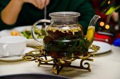 玻璃teaspot用薄荷的茶和在桌上的松子 图库摄影